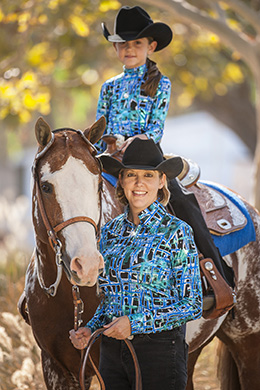 "Perfect partners in the show ring: mother/daughter showgirls wear stunning royal blue blouses in a fitted fashion-forward presentation. ""Dizzy"" blouses from Hobby Horse have metallic foil accents and coordinate with a royal blue saddle blanket. Photo ©2015, Hobby Horse Clothing Co., Inc."